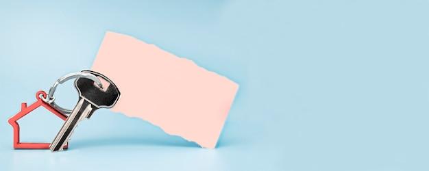 Das konzept der hypothek, des verkaufs und der vermietung von wohnungen und immobilien. schlüsselanhänger in form eines hauses mit schlüssel auf hellblauem hintergrund. papieraufkleber mit platz für text. bannerformat.