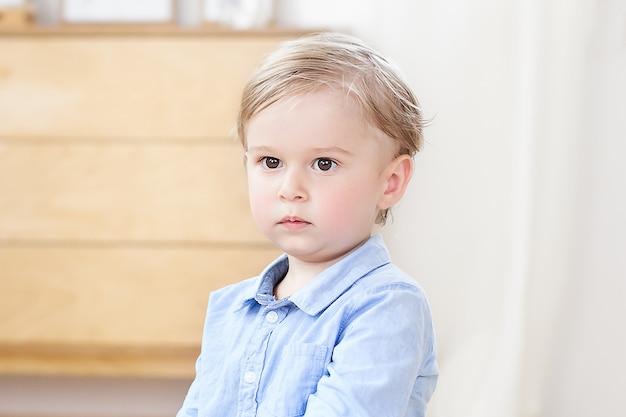 Das konzept der kindheit und der kindlichen entwicklung. das kind ist zu hause. ein nahaufnahmeporträt des gesichtes eines nachdenklichen blonden kleinen jungen. ein kind im kindergarten. beleidigter junge, verärgertes kind. trauriger junge
