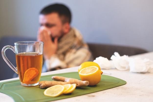 Das konzept der krankheit, winterzeit. schwarzer tee, zitrone und ingwer auf dem tisch,