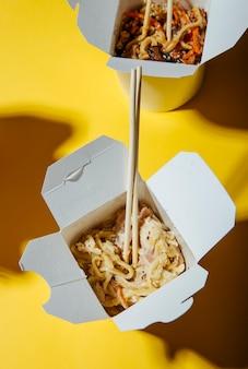 Das konzept der lebensmittellieferung auf einem gelben hintergrund nudeln in kisten