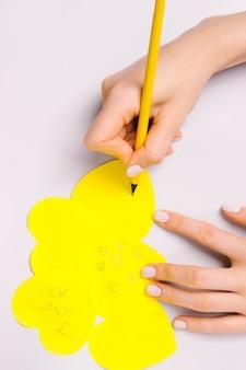 Das konzept der liebe und des feiertags auf den gelben herzen des weißen hintergrunds mit einer liebeserklärung.