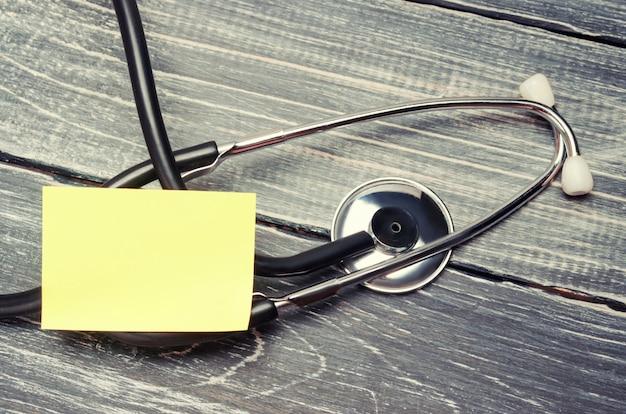 Das konzept der medizin und der krankenversicherung. stethoskop und aufkleber auf einem hölzernen hintergrund