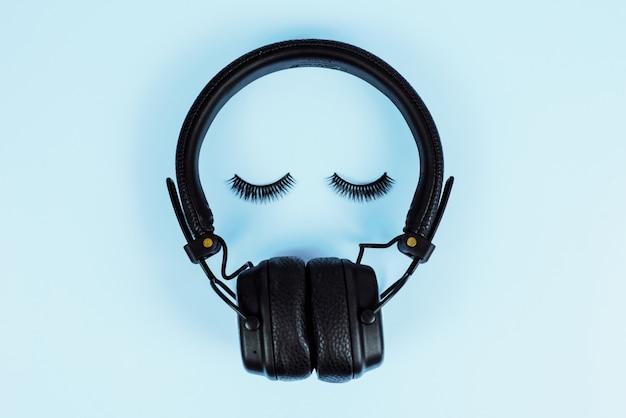 Das konzept der musik. wimpernverlängerungskonzept. bluetooth-kopfhörer mit falschen wimpern auf einem blauen pastellhintergrund