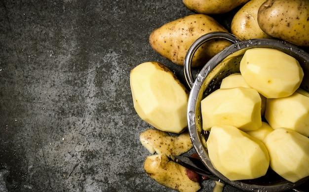 Das konzept der nassen geschälten kartoffeln auf einem steinhintergrund