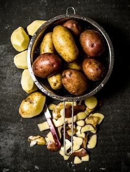 Das konzept der nassen kartoffeln im sieb auf dem steintisch