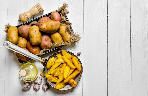 Das konzept der ofenkartoffeln in einer pfanne mit gewürzen auf einem weißen holztisch
