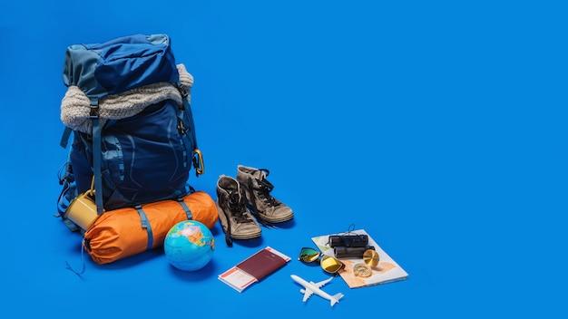 Das konzept der organisation von ausrüstung für das reisen legen sie das gepäck auf. konzeptzubehör für reisende urlaub mit karte, reisepass auf blauer farbwand. reiserucksack