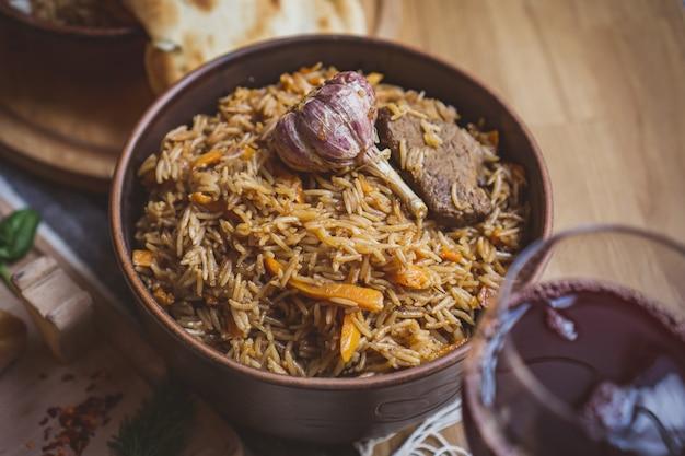 Das konzept der orientalischen küche. hausgemachter georgischer usbekischer pilaw oder plov vom lamm, serviert in gusseisernem kochgeschirr.