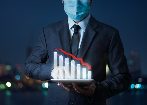 Das konzept der pfeile der wirtschaftskrise fällt, der aktiensturz des grafikers zeigt auf dem tablet mit dem geschäftsmann, was auf die wirtschaftliche rezession hinweist, die eintreten wird