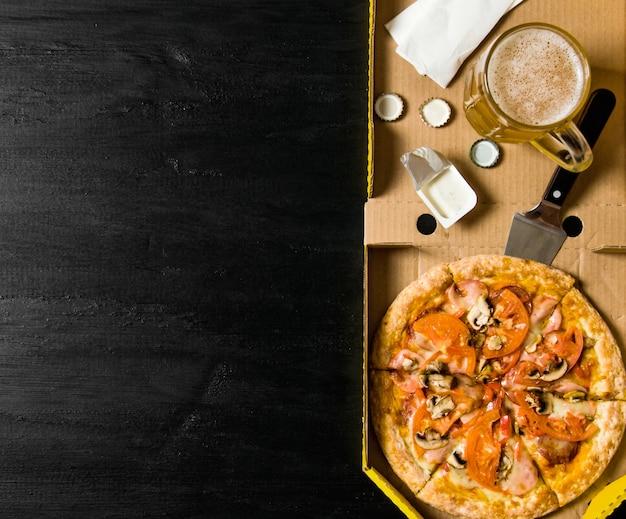 Das konzept der pizza mit bier. pepperoni-pizza mit bier auf einem holztisch