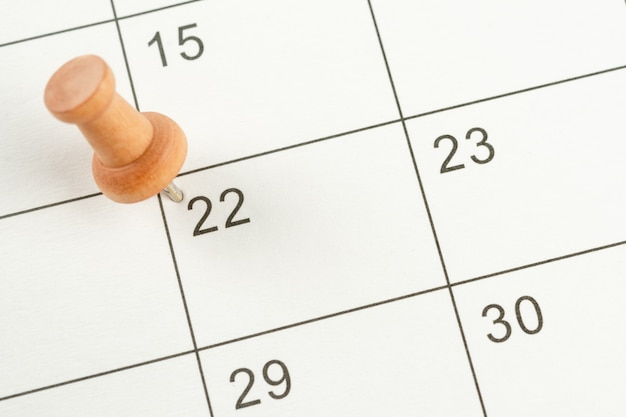 Das konzept der planung und frist mit stecknadel am kalenderdatum