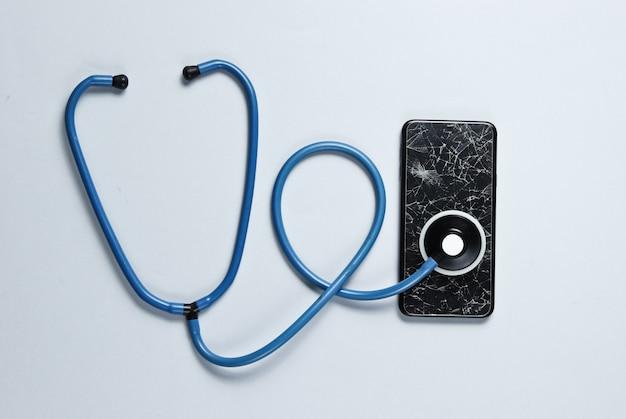 Das konzept der serviceunterstützung beim zusammenbruch des smartphones. glasscherben eines smartphones, stethoskop auf grauem tisch