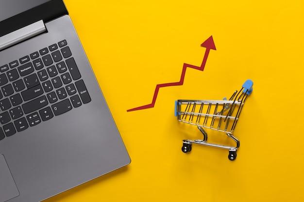 Das konzept der steigenden umsätze. onlinegeschäft. laptop, einkaufswagen mit wachstumspfeil auf gelb
