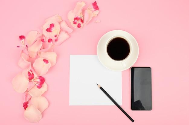 Das konzept der tagesplanung. eine tasse kaffee, weiße karte, rosa blumen. flach liegen