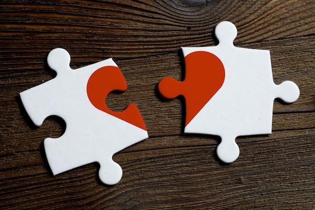 Das konzept der trennung und nicht der gegenseitigen liebe. stücke eines weißen puzzlespiels auf einem holztisch