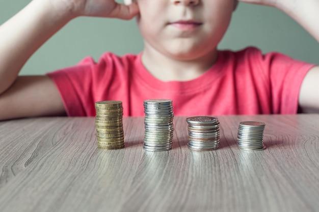 Das konzept der wirtschaftlichen bildung von kindern. junge baut einen turm mit münzen.