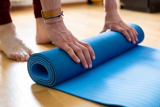 Das konzept der yoga-und fitness-matte in den händen.