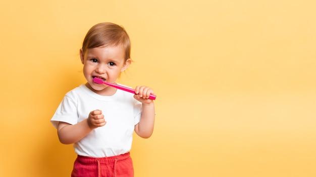 Das konzept der zahnhygiene. ein kleines blondes mädchen putzt sich die zähne mit zahnpasta. gelber hintergrund. ein platz für ihren text.