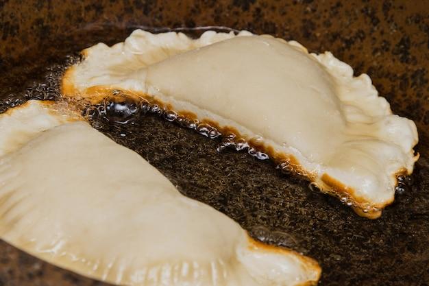 Das konzept des backens zu hause mit rohem teig, golden gebratenem cheburek in einer pfanne mit öl, kochen.