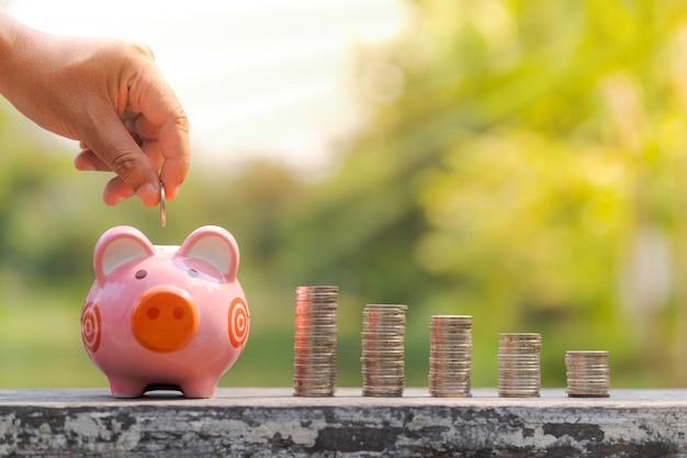 Das konzept des einsparens des geldes, hand, die eine münze in sparschwein über unscharfem gartenhintergrund setzt