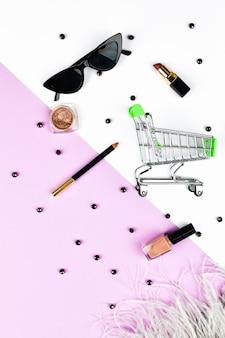 Das konzept des fraueneinkaufs. korb und damenaccessoires. damenaccessoires auf einem rosa raumpastell. schönheits- und modekonzept. draufsicht, flacher minimalismus.