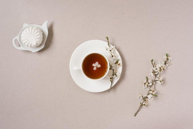 Das konzept des frühlings. eine tasse schwarztee mit apfelblüten und marshmallows auf einem teekannenteller auf beigem hintergrund