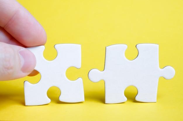 Das konzept des gesamtbildes nach dem letzten detail. ein teil des puzzles wird von den fingern eines mannes neben einem anderen an einer gelben wand gehalten