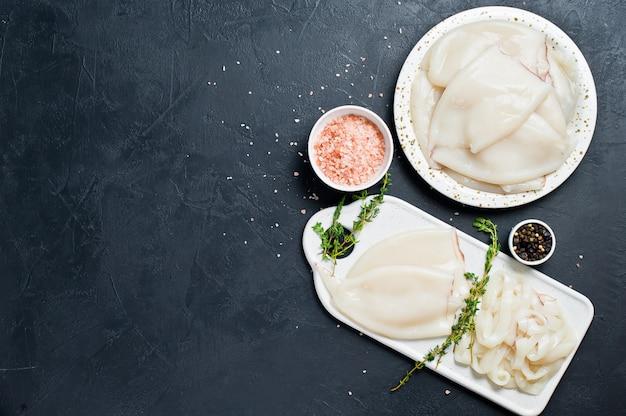 Das konzept des kochens rohen tintenfisch zutaten zum kochen thymian, pfeffer, rosa salz