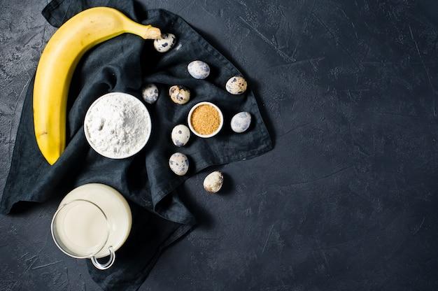 Das konzept des kochens von bananenbrot. zutaten: bananen, butter, wachteleier, zucker, mehl, milch.