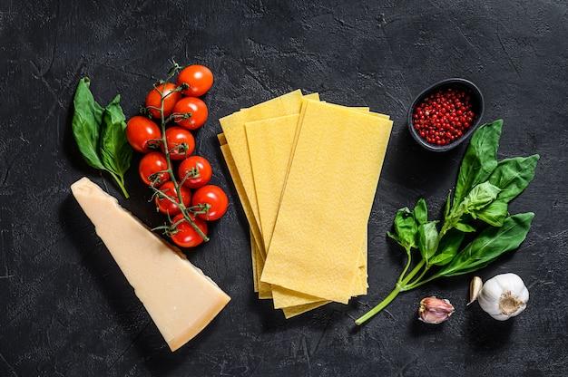 Das konzept des kochens von lasagne. zutaten, lasagneblätter, basilikum, kirschtomaten, parmesan, knoblauch, pfeffer. schwarzer hintergrund. draufsicht