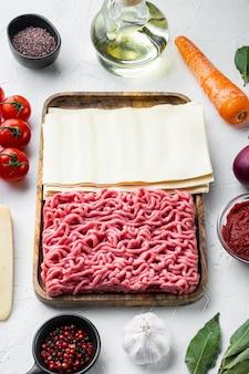 Das konzept des kochens von lasagne. zutaten, lasagneblätter, basilikum, kirschtomaten, parmesan, knoblauch, pfefferset, auf weißem steintisch