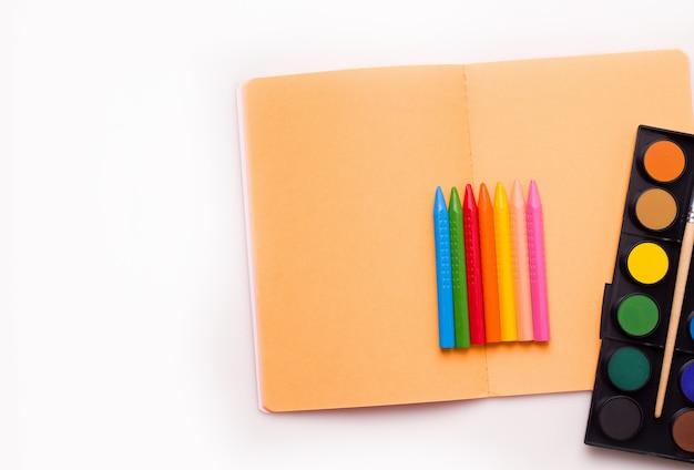 Das konzept des kreativen zeichnens von kindern. buntstifte, notizbuch, farben.