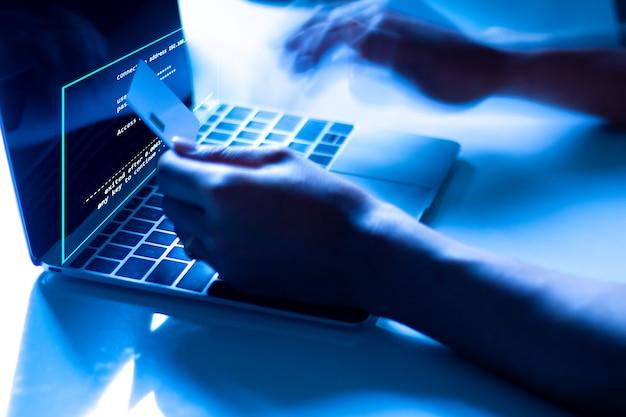 Das konzept des kreditkartendiebstahls. hacker mit kreditkarten auf laptops verwenden diese daten