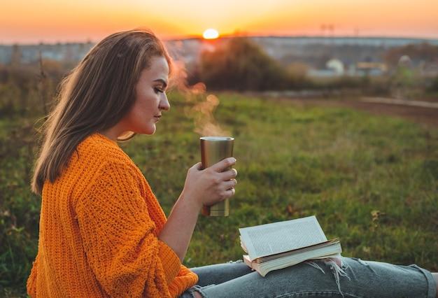 Das konzept des lebensstils und der erholung der familie im freien im herbst. frau las bücher auf plaid mit einer thermotasse. herbst. sonnenuntergang. gemütlich