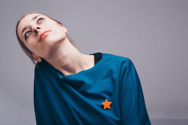 Das konzept des nähzubehörs: brosche in sternform. porträt einer schönen frau in blauer kleidung