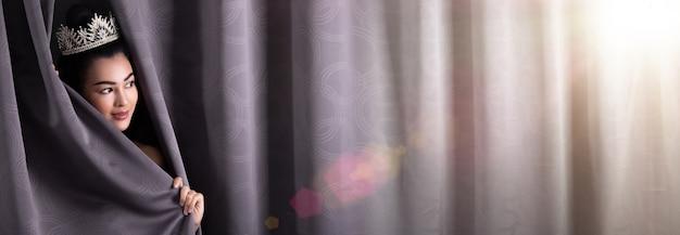 Das konzept des schönen miss pageant queen-wettbewerbs öffnet den bühnenvorhang als türfenster für neue möglichkeiten, leben, zufall und arbeit. asiatische frau ändert alles am nächsten tag nach dem gewinn der diamantkrone.