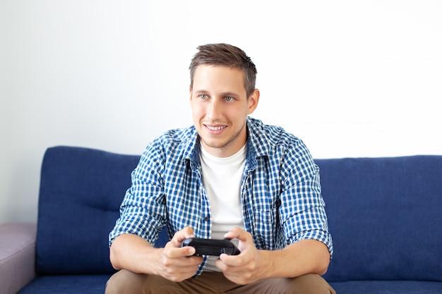Das konzept des spiels. der typ spielt zu hause ein videospiel mit einem joystick. ein lächelnder mann in einem hemd, der auf der couch sitzt, spielt ein videospiel mit einem joystick. computerspielwettbewerb. spieler.