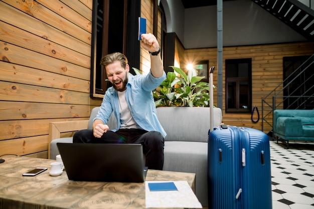 Das konzept des tourismus, reisen. junger mann bereitet sich vor, auf dem sofa sitzend zu reisen