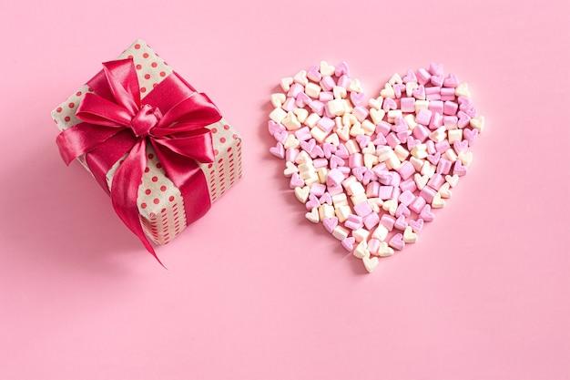 Das konzept des valentinstags. geschenkbox mit roter schleife an rosa wand.