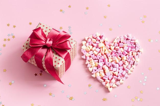 Das konzept des valentinstags. geschenkbox mit roter schleife auf rosa.