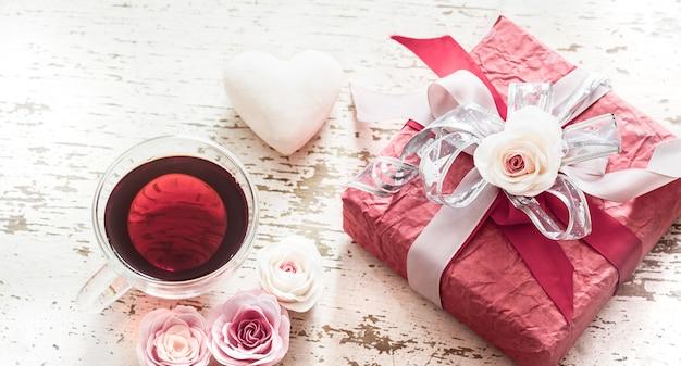 Das konzept des valentinstags und des muttertags, eine rote geschenkbox mit einer schleife mit rosen und einer tasse tee auf einem hellen hölzernen hintergrund