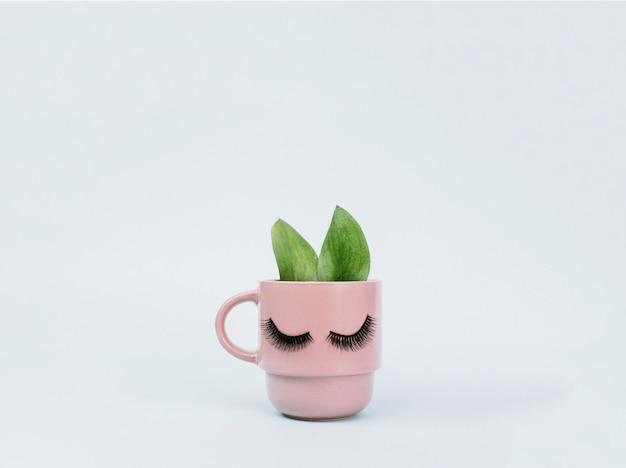 Das konzept des weiblichen morgens und des natürlichen kaffees. rosa becher morgenkaffee mit den ohren wie ein kaninchen von den grünen blättern auf einem blauen pastellhintergrund