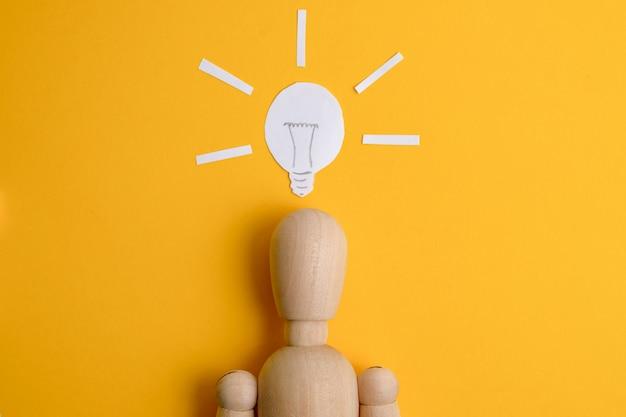 Das konzept einer gefundenen geschäftsidee oder eines startups. hölzernes mannequin auf einem gelben hintergrund unter einer gemalten glühlampe.