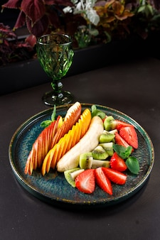Das konzept einer gesunden ernährung. obst- und beerenplatte - apfel, orange, banane, kiwi, erdbeere, minze