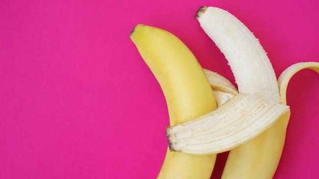 Das konzept eines freundlichen paares. banane wie ein ehemann umarmt einen anderen wie eine ehefrau. idee für ein schwules paar. einfarbiger rosa hintergrund.