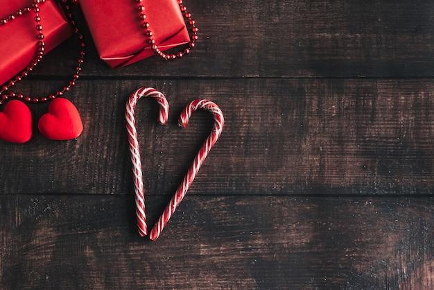Das konzept eines guten rutsch ins neue jahr. weihnachtsgeschenke, lutscher liegen auf einem hölzernen hintergrund. der blick von oben