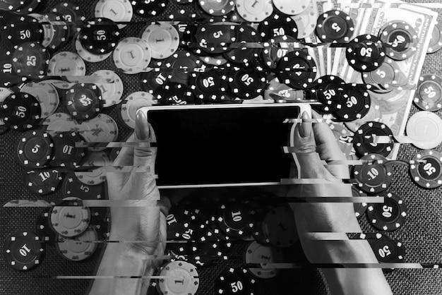 Das konzept eines online-casinos: spielkarten, wettchips und ein smartphone mit kopienraum in frauenhänden. ansicht von oben. rauch zum foto hinzugefügt