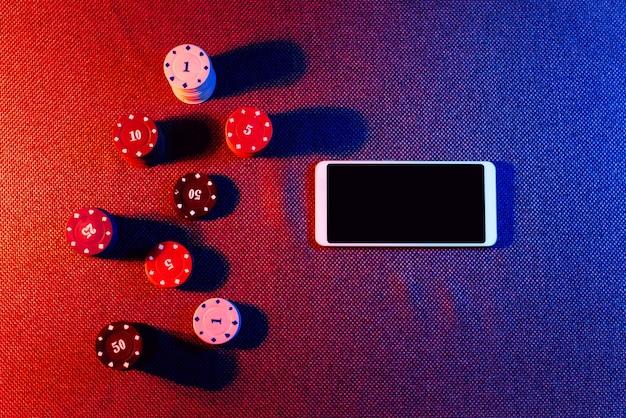 Das konzept eines online-casinos: wettchips und ein smartphone mit grünem hintergrund mit kopienraum. ansicht von oben.