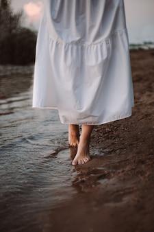 Das konzept eines romantischen sommerspaziergangs barfuß einer frau, die bei sonnenuntergang an der küste entlang geht