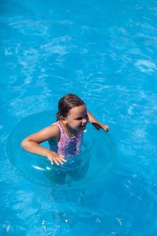 Das konzept eines sommerurlaubs ein fröhliches kind hat eine gute zeit im sauberen, transparenten wasser der ...
